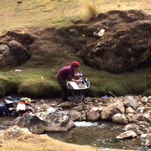 woman washing clothes in cold stream she hauled down by wheelbarrow