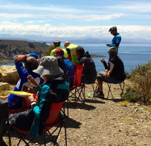 cyclists enjoying lunch during break - overlooking ferry on Lake Titicaca
